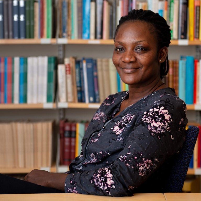 Betty Nannyonga sitter i ett rum fyllt med bokhyllor. Hon ler och tittar in i kameran. Hon har en grå blus med rosa blommor.