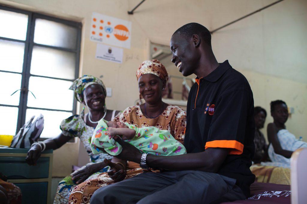 Två kvinnor och en man tittar på ett spädbarn som mannen håller i armarna.