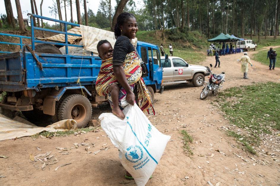 Bilden visar när World Food Programme (WFP) levererar mat till människor som bor i ett område som drabbats av ebola i Demokratiska republiken Kongo 2019. En kvinna bär sitt barn på ryggen och håller i ett av WFP:s matpaket.