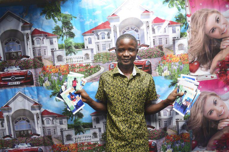 Peter står framför en fotovägg och håller upp examensbilder.