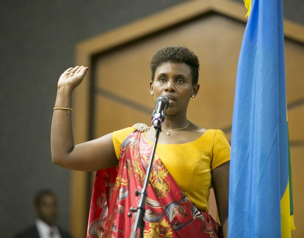 Claudine Uwera svärs in som minister. Hon står bredvid Rwandas flaggs och håller upp sin högra arm. Framför henne står en mikrofon.