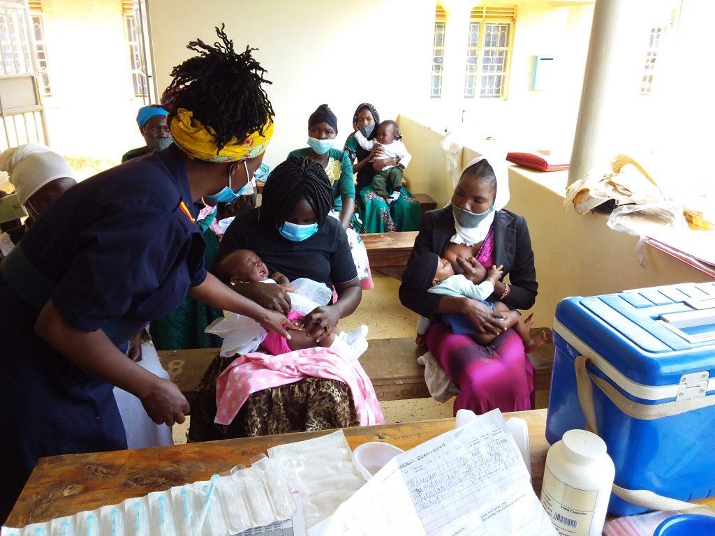 Några kvinnor sitter på hälsoklinikens bänkar och håller i spädbarn. En person ur personalen undersöker ett av dem.