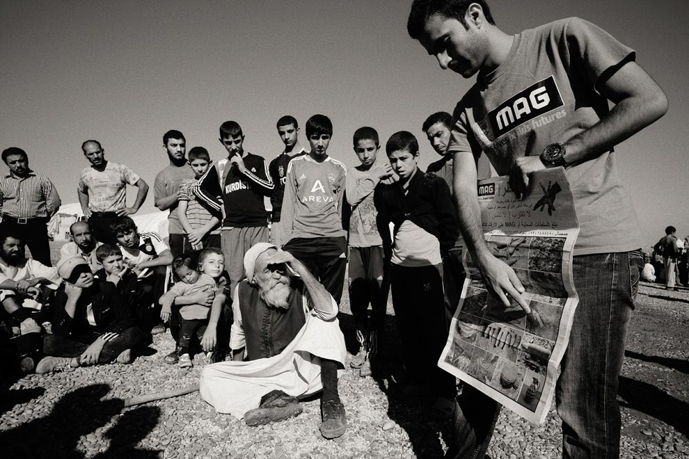 Tjugotal personer står och sitter på en grusplan medan de deltar i en kurs om minor. De lyssnar på en man som står närmast kameran. Mannen pekar på en affisch som han håller i.