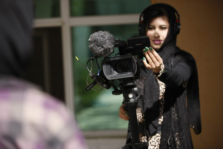 En kvinna med hörlurar håller i en kamera som hon riktar mot en person i förgrunden.