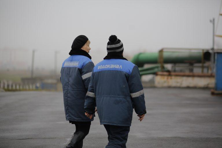 Två av reningsverkets anställda går med ryggarna mot kameran. Reningsverket syns i bakgrunden.