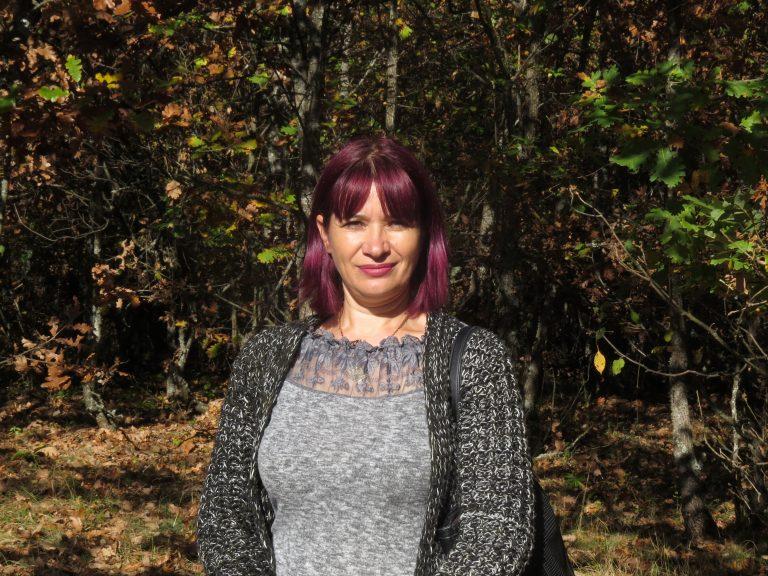 Iskra står på en gräsmatta och tittar in i kameran. Bakom henne syns träd och buskar.