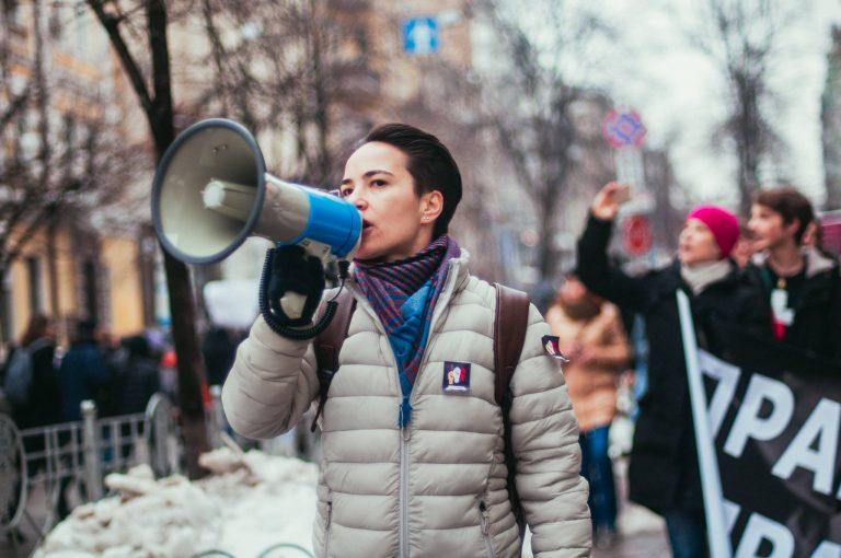 Olga Shevchenko går i ett demonstrationståg. Hon använder en megafon. I bakgrunden syns fler demonstranter.