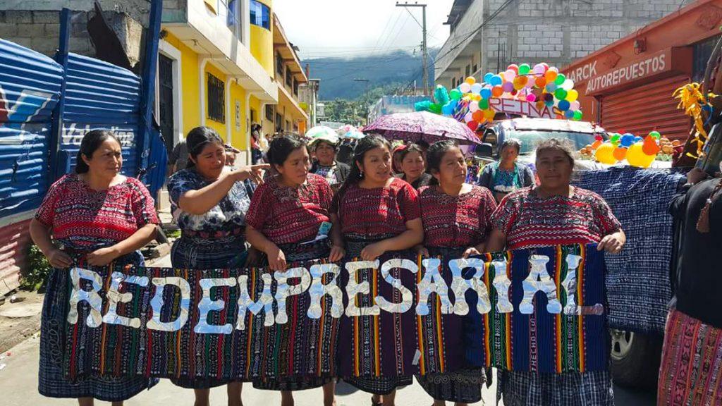 """Sex kvinnor som tillhör Evelyns marknadsnätverk står på en gata. De håller en skylt mellan sig med texten """"Redempresarial"""". Bakom kvinnorna syns resten av paraden kvinnorna går i."""