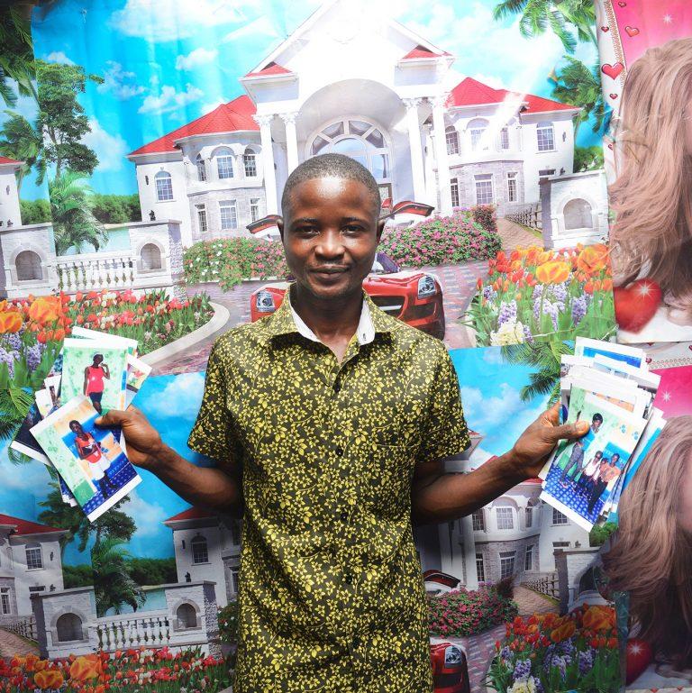 En ung person står framför en bild på ett palats och håller i flera broschyrer.
