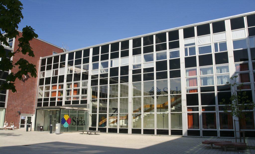 Huvudingången till Sidas huvudkontor på Valhallavägen i Stockholm. Himlen är blå.