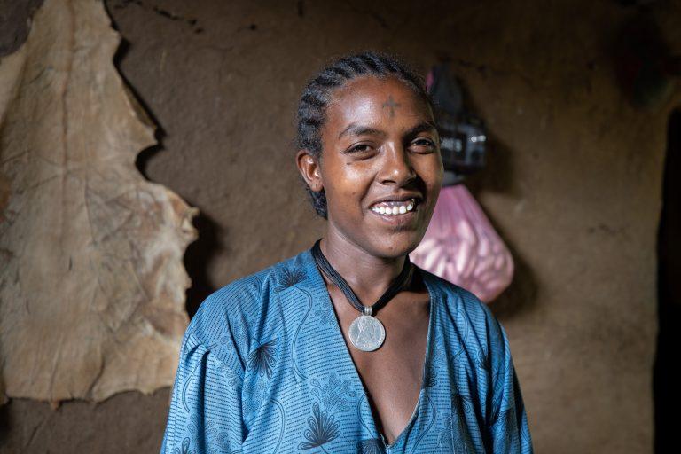 Emaye Yalew ler och tittar in i kameran. Bakom henne syns en brun vägg.
