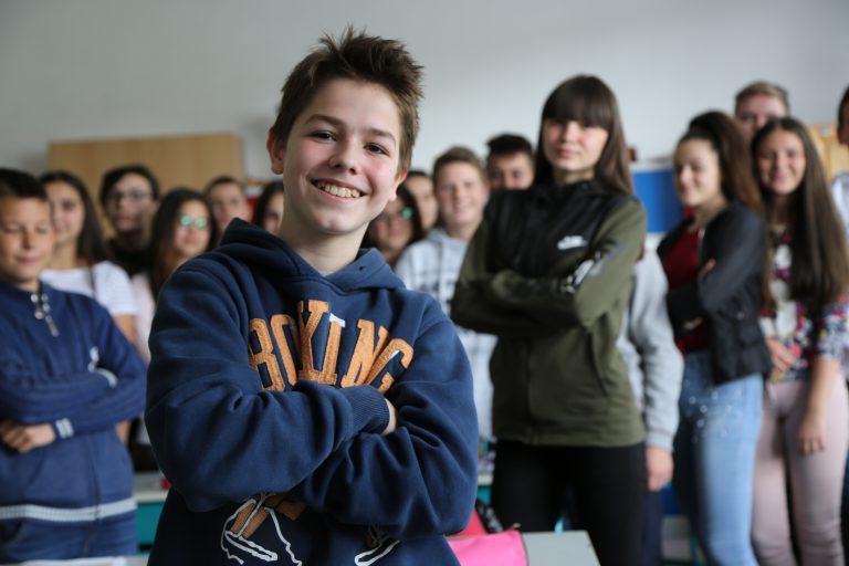 Eldar står i förgrunden och tittar in i kameran. Bakom honom syns hans klasskamrater.