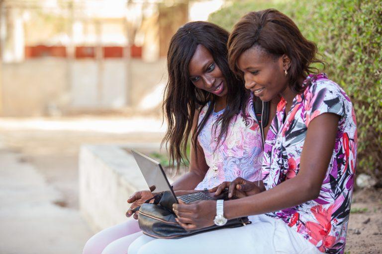 Två kvinnor sitter bredvid varandra på en låg mur och tittar i samma laptop.