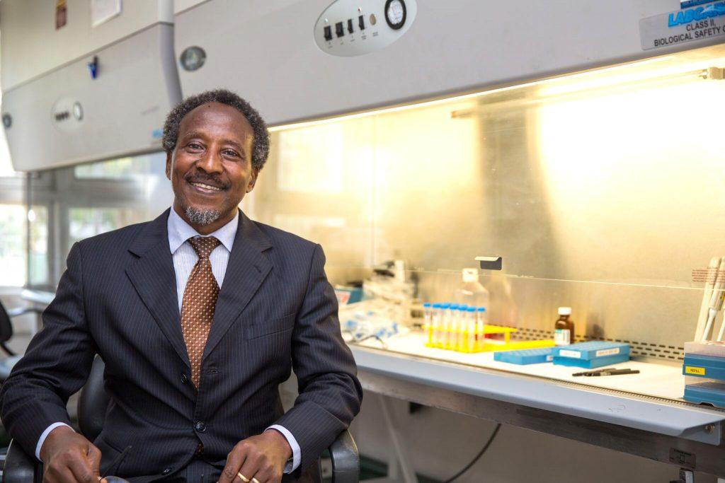 Professor Lyamuya sitter på en stol och tittar leende in i kameran. I bakgrunden, till höger om honom syns labbutrustning .