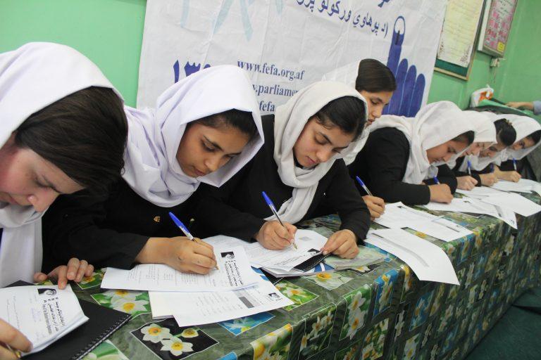 Sju unga kvinnor i skoluniform sitter på rad vid ett bord och fyller i papper.