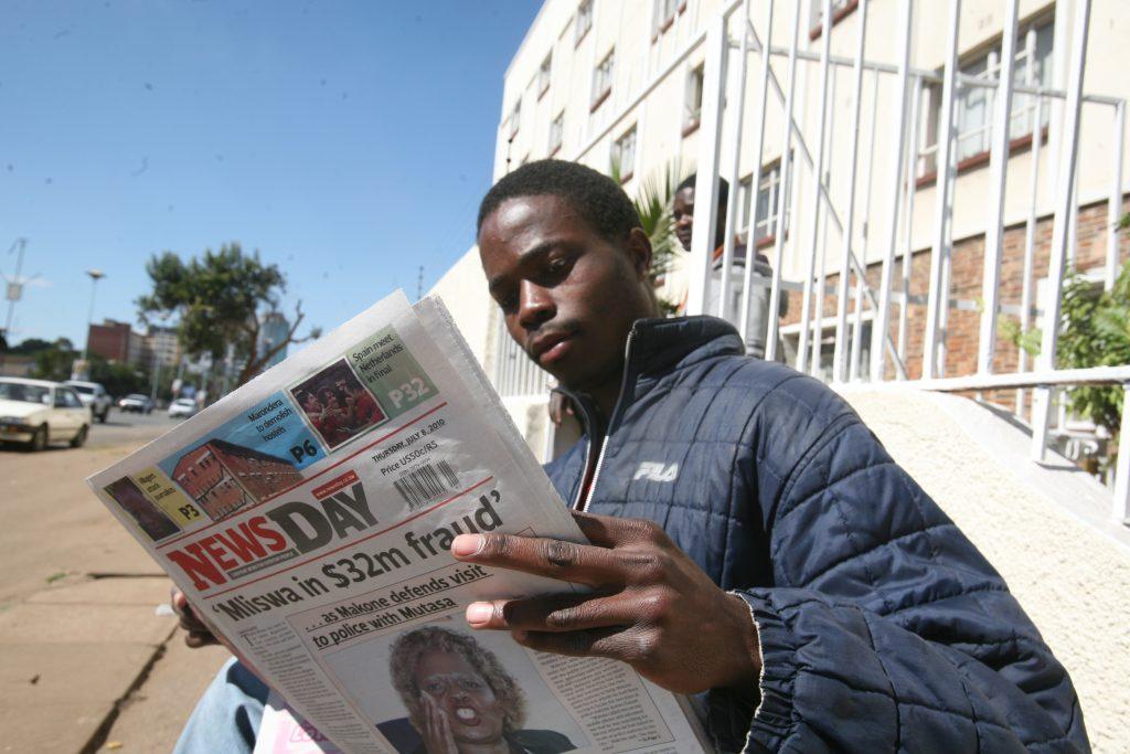En man sitter på en bänk och läser tidningen 'NewsDay'. Bakom honom syns byggnader och bilar.