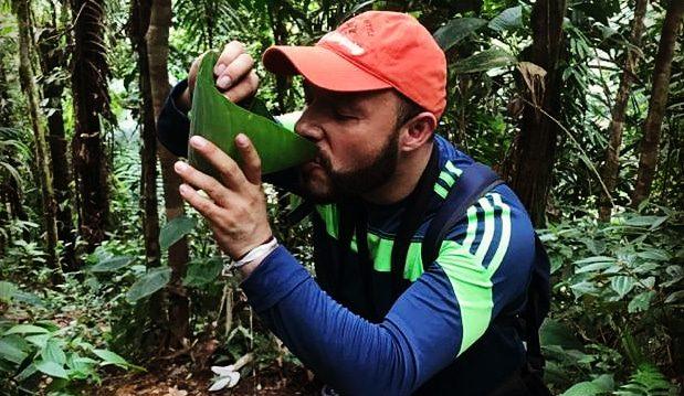 En man, Oscar, står i skogen och dricker vatten ur ett stort skålformat blad.