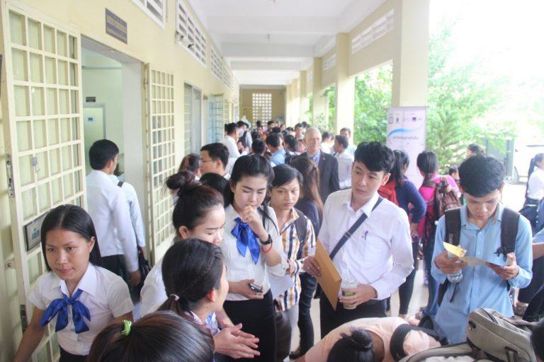 Många ungdomar står vid ett bord. De håller papper i händerna. Ungdomarna är klädda i skoluniformer.