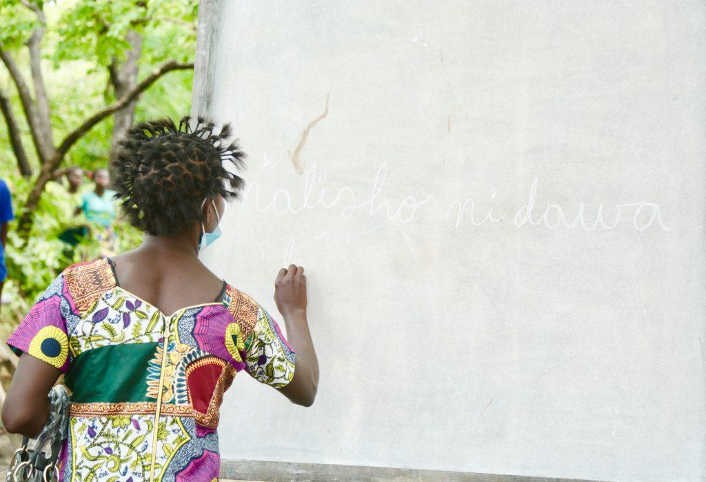 Kvinnan Kyungu Ngandu Inankulu skriver med skrivstil på en stor frå tavla. Hon är fotad snett bakifrån.