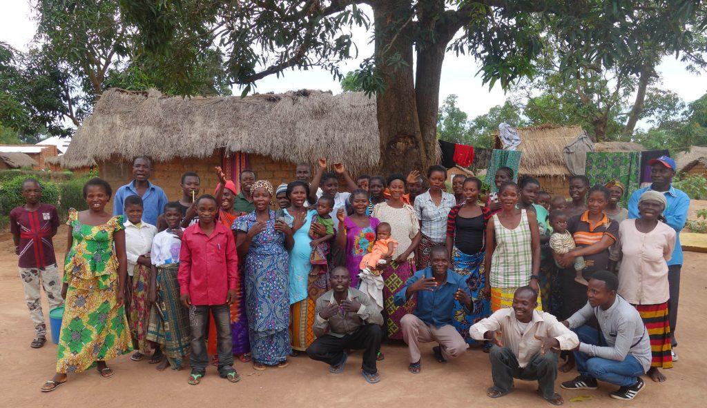 Ett 30-tal män, kvinnor och barn står eller sitter framför ett tegelhus med halmtak för att bli fotograferade. Kvinnorna har färgglada klänningar eller kjolar. De tillhör en Dimitraklubb i DRC Kongo.