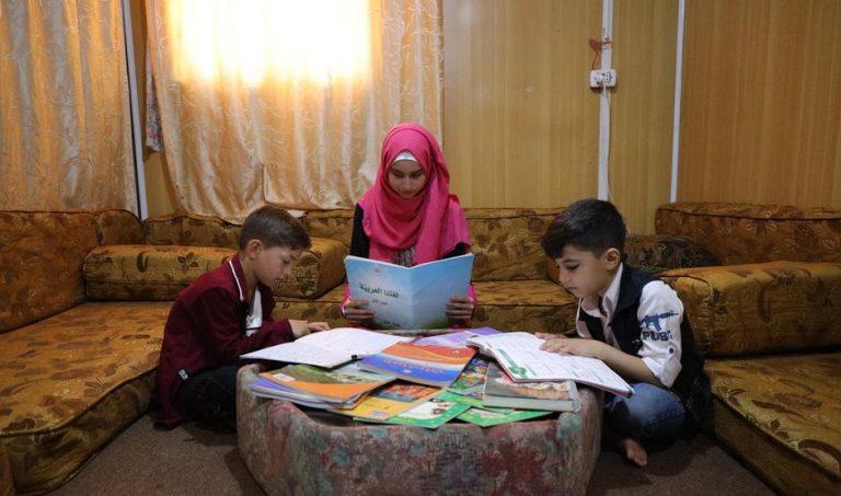Tre barn sitter på golvet och läser.
