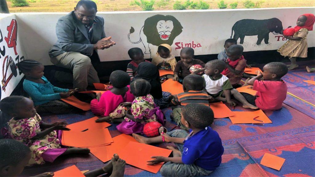 Läraren Emmanuel Matola leker med flera små barn som ritar på papper.
