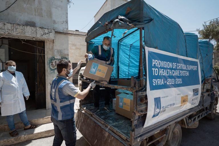Två män lastar en lastbil med kartonger.