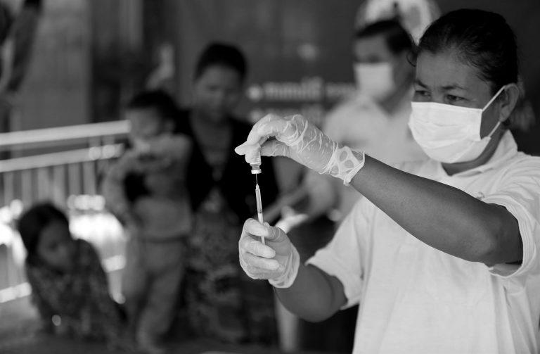 Kvinna som håller i en spruta med covid-19-vaccin i Kambodja.