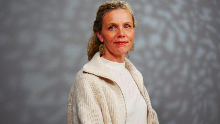En kvinna i vit kofta framför en grå bakgrund