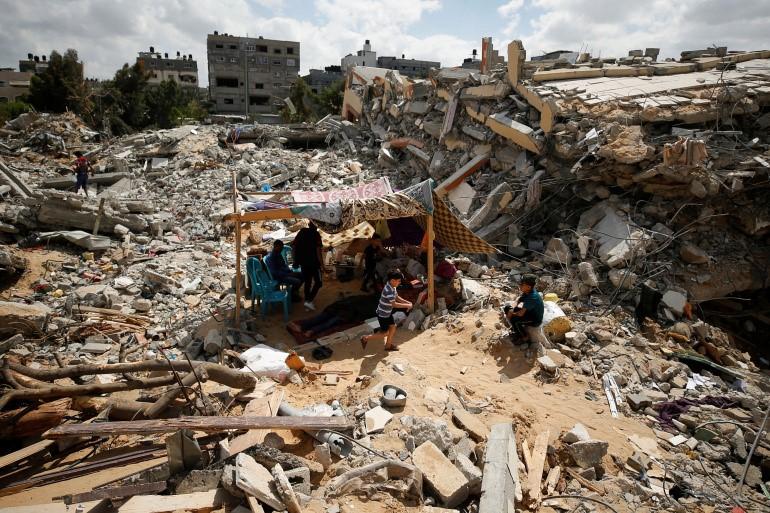 Några människor sitter under en presenning i resterna av ett bombat hus