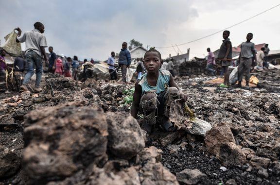 Ett barn i trasiga kläder sitter på huk bland lavastenar. I bakgrunden finns flera barn.