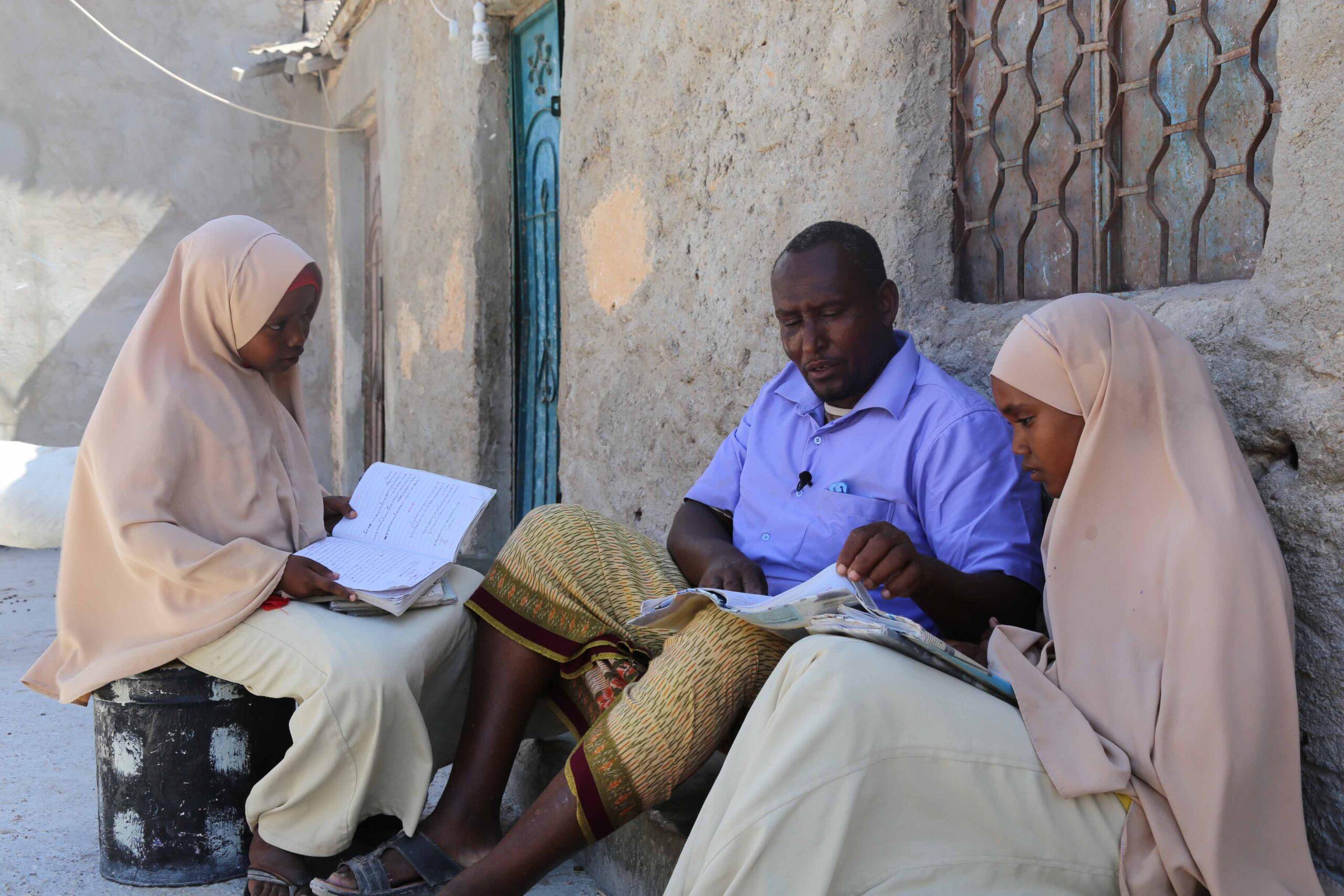 En man hjälper sina barn med läxorna