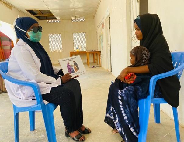En mamma med sitt barn och en sjuksköterska.