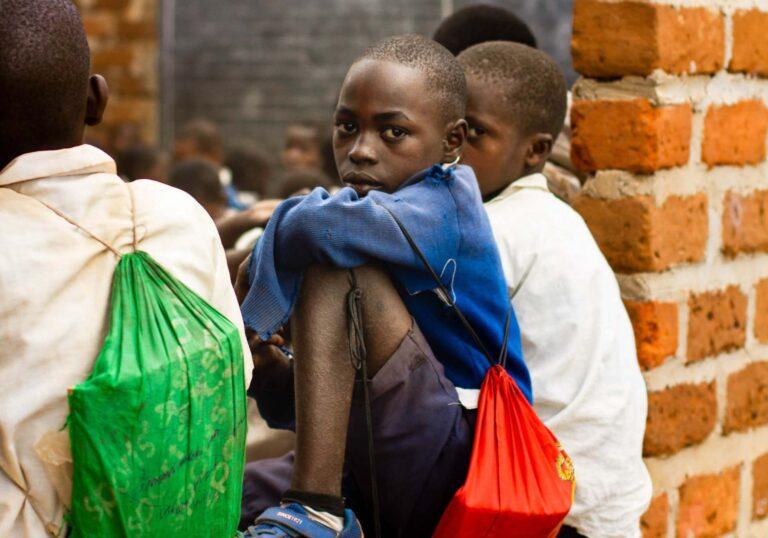 Skolpojkar i Tanzania på en mur
